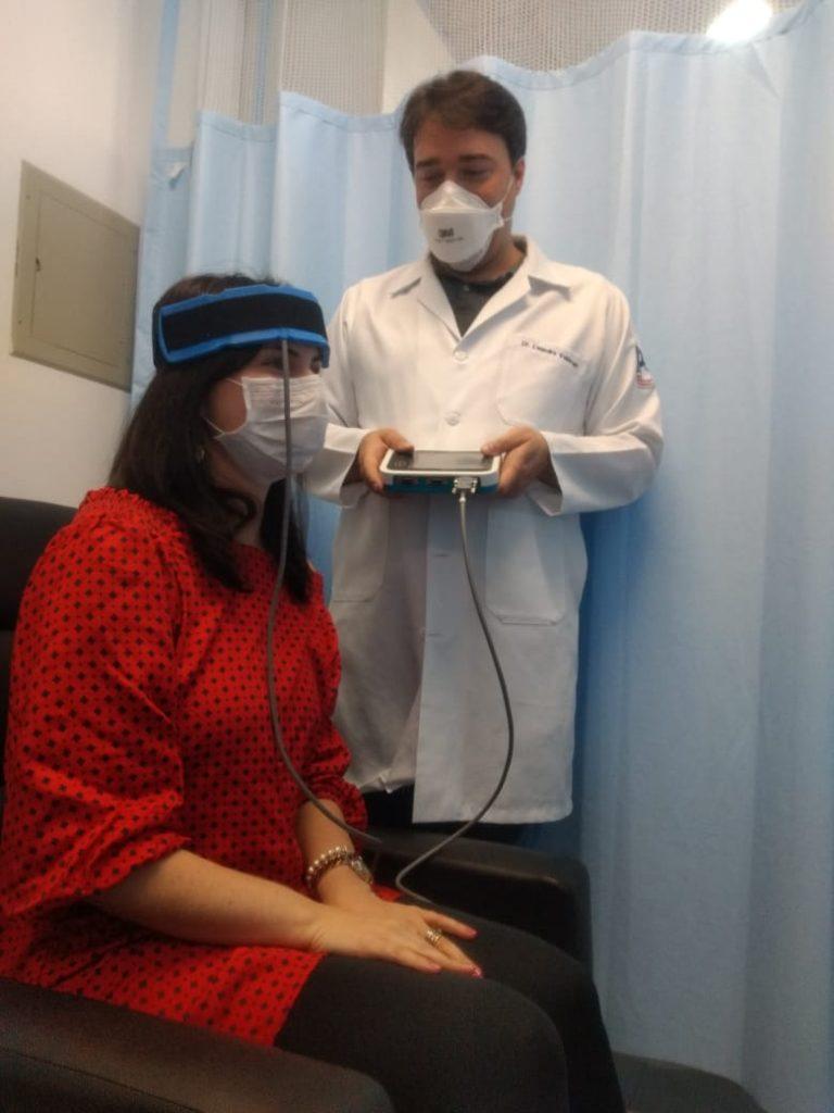 O psiquiatra Leandro Valiengo faz uma simulação de como o aparelho é posicionado na cebeça do paciente (Divulgação)